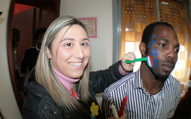 L'operatrice Rossana Licari pittura la bandiera italiana su un migrante.