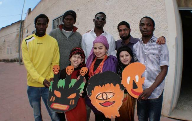 """Alcuni bambini della scuola elementare """"Luigi Pirandello"""" con le maschere tribali e alcuni migranti ospiti della Fondazione."""