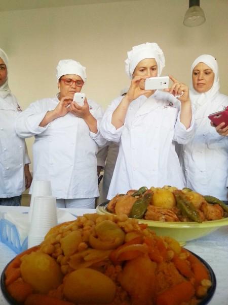 Le donne tunisine fotografano i piatti di cous cous da loro realizzati.
