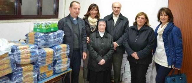 I soci del Rotary mentre consegnano i beni di prima necessità al parroco don Giuseppe Titone della parrocchia del quartiere Mazara Due.