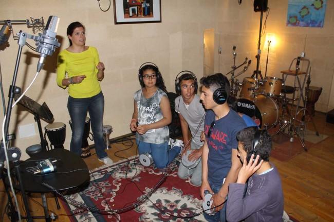 Alcuni ragazzi durante la registrazione del brano in studio, con Debora Messina.