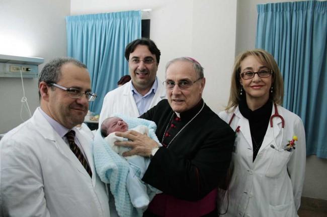 Enzo Agate, Vito Cavallaro, Anna Bono e il Vescovo che tiene in braccio il piccolo Manuel Catalano, nato proprio durante la celebrazione della messa in ospedale.