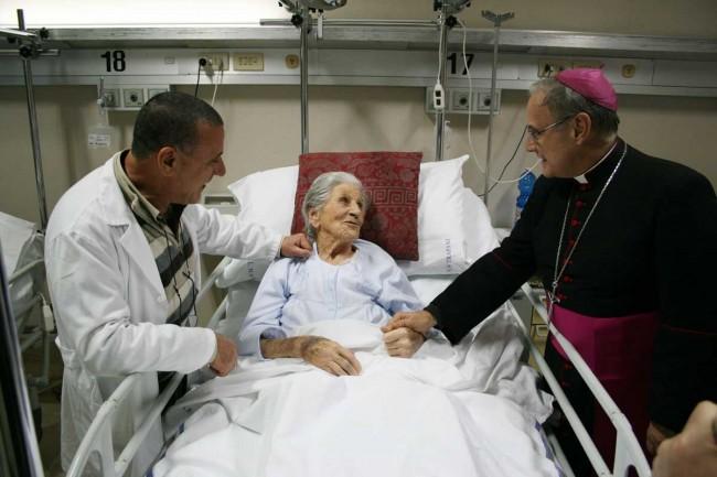 Il Vescovo visita un'ammalata nel reparto di ortopedia: ad accompagnarlo il dottor Bartolo Lupo.