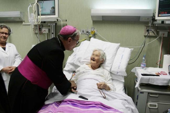 Il Vescovo saluta un'ammalata in terapia intensiva nel reparto di Cardiologia.