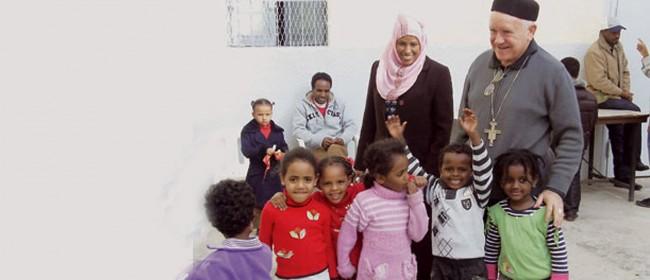Il Vescovo di Tripoli, monsignor Giovanni Martinelli insieme a bambini libici.