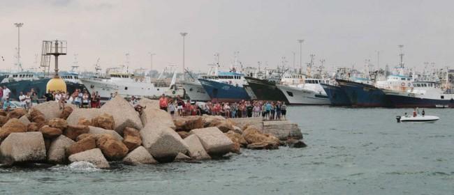 """Fedeli e curiosi sul molo del porto nuovo assistono al passaggio del peschereccio """"Afrodite"""" con a bordo il simulacro di San Vito."""