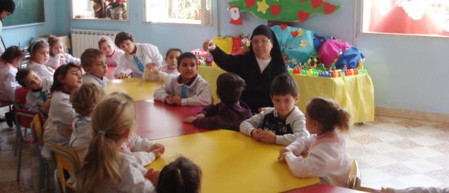 Una suora insieme ai bambini dell'asilo dell'istituto.