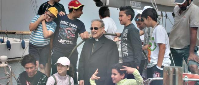 """Il Vescovo a bordo di una barca a vela nel porto di Mazara del Vallo, in mezzo ai ragazzi che hanno partecipato al """"Progetto Ulisse""""."""