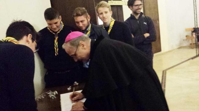 Il Vescovo in visita alla mostra, mentre firma il registro dei visitatori.