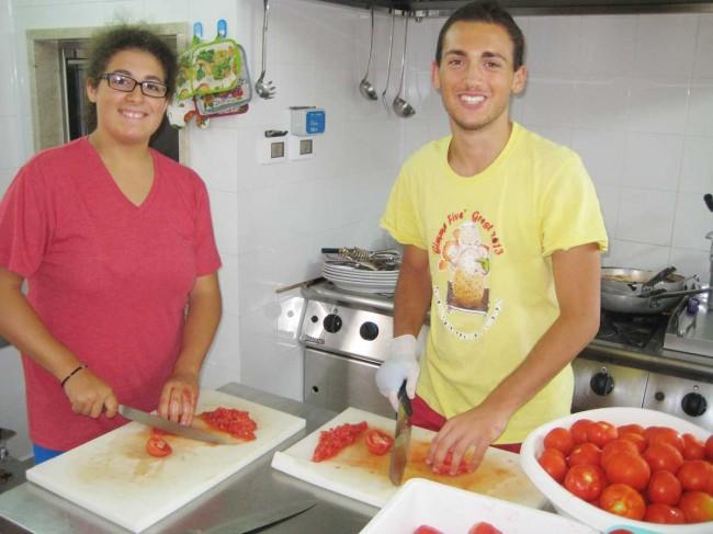 Due ragazzi mentre preparano in cucina.